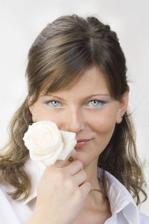 untitled key: nice and young woman with roses in her hands smelling and smiling with her fair eyes