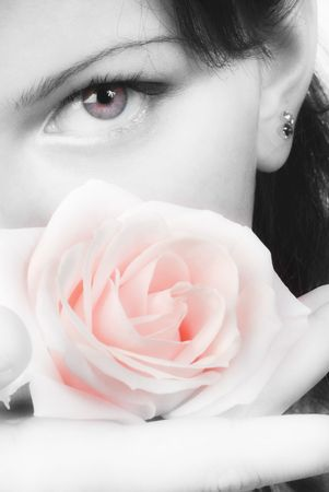 nice black and white portrait of a young woman with roses in her hands smelling and smiling with her fair eyes photo