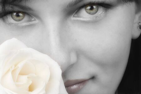 nice black and white portrait of a young woman with roses in her hands smelling and smiling with her fair eyes Stock Photo - 958326