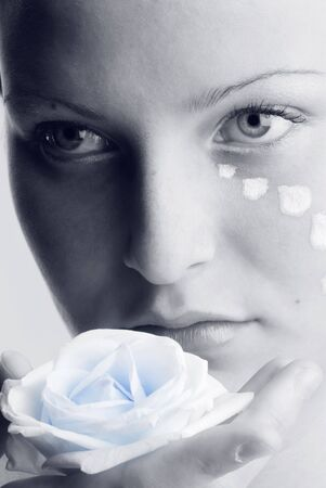 beautiful portrait in black and white of a girl looking sweetly with painted face and a rose in her hand photo
