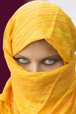 attactive and strong eyes behind an orange scarf used like a burka Stock Photo - 958372