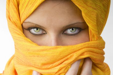 seductive expression: attactive and strong eyes behind an orange scarf used like a burka Stock Photo