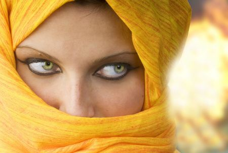 attactive and strong eyes behind an orange scarf used like a burka photo