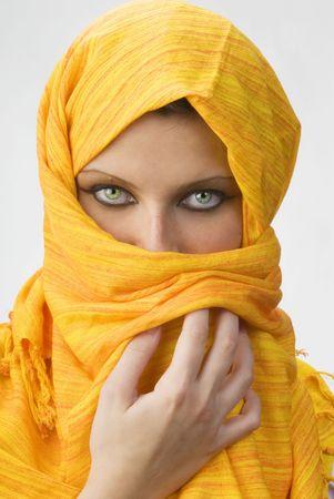 ojos attactive y fuertes detrás de una bufanda anaranjada usada como un burka