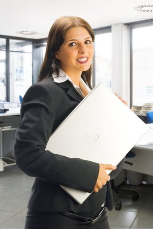 a cute brunette with a black jacket keeping a laptop on her arm Stock Photo - 1066220