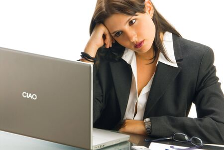 tailleur: a white collar worker in formal black tailleur sitting at her desk  working with a computer and having an expressive face