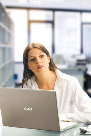 tailleur: a white collar worker dressing a white shirt sitting at her desk  working with a computer and having an expressive face Stock Photo