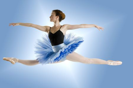 dancer in blue tutu jumpig on a shining blue backgroundr photo