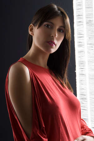 young brunette with a red skirt on a black background  Stock Photo - 1456940