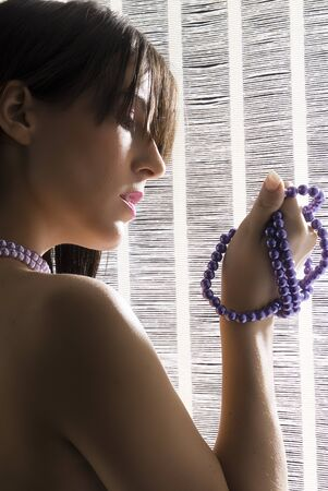 young and cute brunette with naked shoulder playing with a pearl string Stock Photo - 1456944