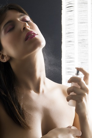 eau: a young and cute woman applying perfume on her neck