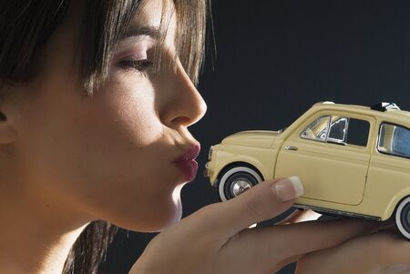 nice and young brunette kissing with an italian style car,fiat 500 photo