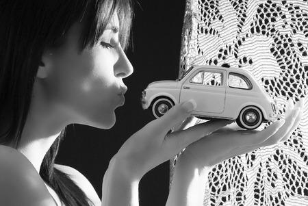 mooie en jonge brunette kussen met een Italiaanse stijl van de auto, Fiat 500