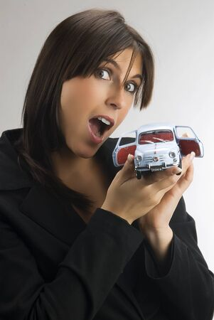 talian: a young and cute brunette looking in camera with surprise and showing a model of an italian car, fiat 600