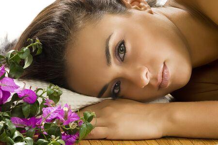 een mooi portret van jongeren en schattige brunette layng op een houten tapijt met bloemen naast haar Stockfoto