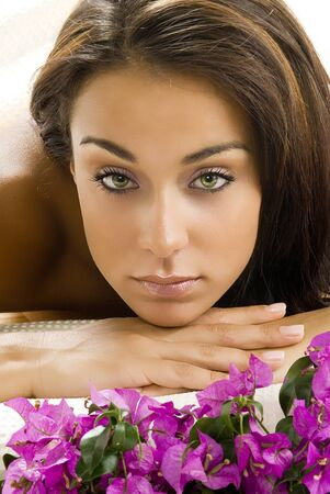 a nice portrait of young and cute brunette layng down on a wood carpet with flowers near her Stock Photo
