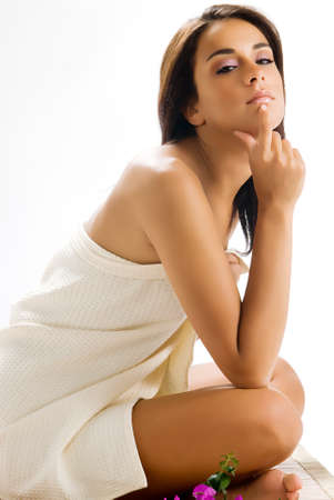 beige lips: nice and young woman sitting on a wood carpet wearing a white towel Stock Photo