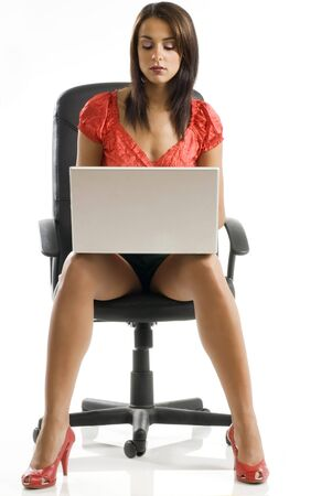 sensual woman in black and red dress sitting on a black chair and writing on the computer Stock Photo