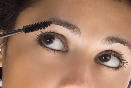 close up of a nice and young woman applying mascara on her eyes photo
