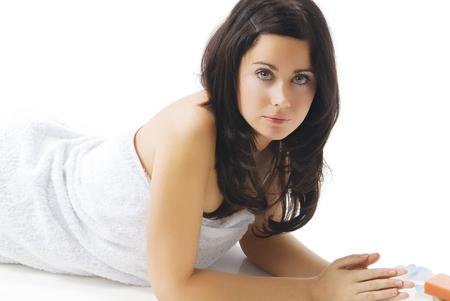 fair skin: cute una mujer joven con cabello oscuro y piel blanca por el que se establecen en el suelo cerca de colorated jab�n y p�talos