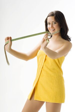 kilograms: pretty young brunette wearing a yellow towel and measuring her legs making funny face Stock Photo