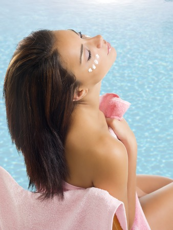 woman in towel: nice brunette wearing a pink towel with cream on face near a swimming pool Stock Photo