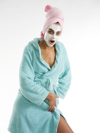 revitalize: cute and nice girl with face cream mask posing and making face Stock Photo