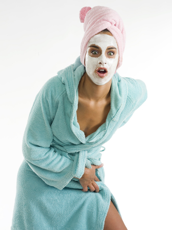 nice girl: cute and nice girl with face cream mask looking in camera with surprise