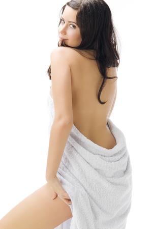 sensueel en schattige jonge brunette draagt een witte handdoek spelen met de camera en maakt sexy pose