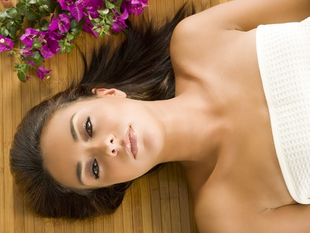 portrait of a beautiful brunette laying down on a wood carpet  Stock Photo