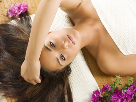 sweetly: beautiful brunette laying down in a spa with long and open hair and looking sweetly in camera Stock Photo
