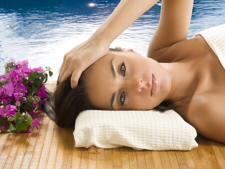 very cute brunette with wonderful eyes laying down on a carpet near a swiming pool Stock Photo - 1665109