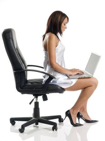 sensuele vrouw draagt een grijze jurk zit op een zwarte stoel en schriftelijk op haar laptop