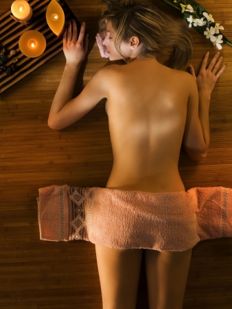 sensual massage: cute woman relaxing herself in a spa with a warm light around Stock Photo