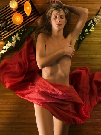 young and beautiful woman laying down in relax in a spa with candle and flowers around her