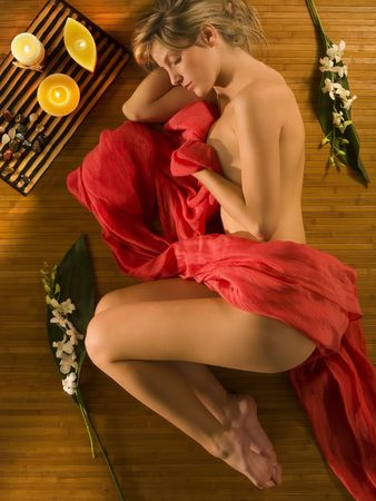 beautiful young blond woman relaxing her self over a wood carpet in sweetly pose
