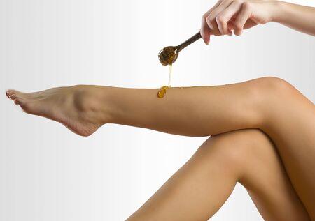 woman putting depilatory wax on her leg like honey  Stock Photo