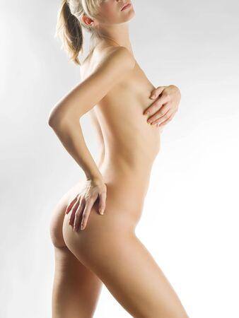 een mooie jonge vrouw toont haar naakte lichaam