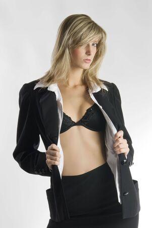 rubia y atractiva mujer joven en traje formal negro mostrando su sensual sujetador a plantear  Foto de archivo - 2135455