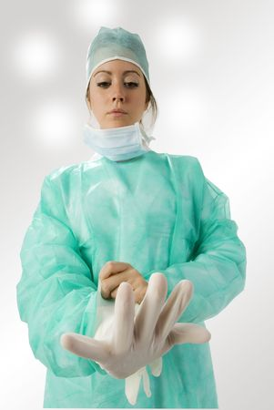 assistent: an assistent putting on her gloves before the operation