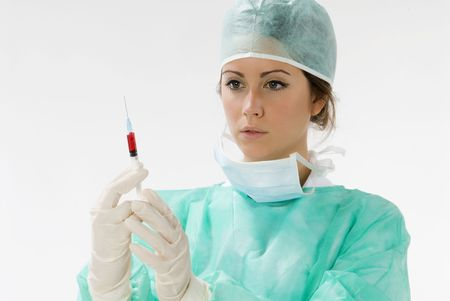 a young nurse in operation dress with a syringe full of blood