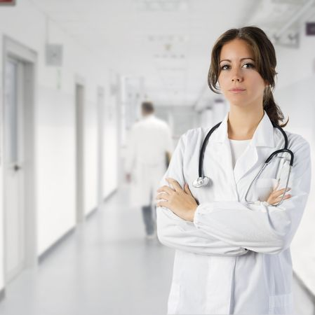 cute brunette in white medical gown   and a stethoscope in an hospital photo