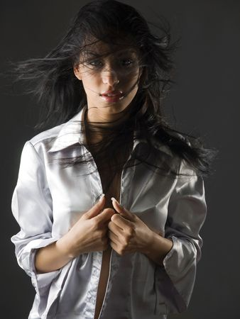 beautiful portrait of a young and very cute latina girl with a fatal look and the hair flying on her face Stock Photo