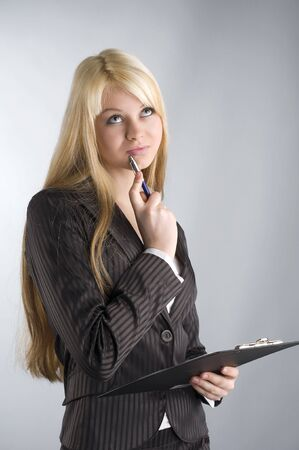 tailleur: pretty girl with blond hair and blue eyes and a pen near lips