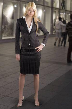 cute blond girl in formal dress near a shopping center photo