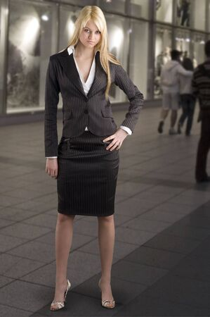 tailleur: cute blond girl in formal dress near a shopping center