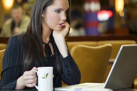 beautiful young woman sitting in a bar with laptop and cup of tea