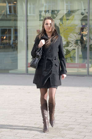 tailleur: cute girl with black coat walking on in sunny day near a shop center Stock Photo