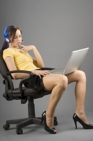office worker sitting down with the laptop on her legs in sexy pose photo