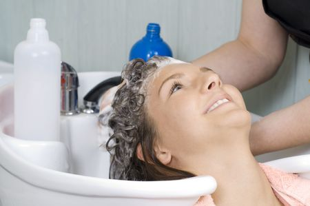 brunette in a salon getting washed her hair with shampoo photo